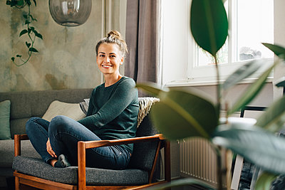 Portrait of smiling woman sitting on armchair at home - p426m2138435 by Maskot