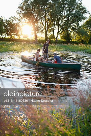 Drei Jungen in einem Kanu auf einem Teich, Haus Strauss, Bauernkate in Klein Thurow, Roggendorf, Mecklenburg-Vorpommern, Deutschland - p1316m1160536 von Hauke Dressler