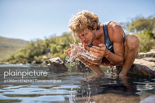 Junger Mann erfrischt sein Gesicht mit Wasser - p1355m1574213 von Tomasrodriguez