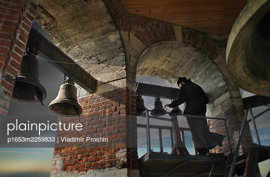 Bell ringer in old bell tower starts to pull the bells  - p1653m2259833 by Vladimir Proshin