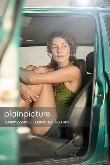 Contemplating woman with folded legs sitting in car - p300m2224990 by LOUIS CHRISTIAN