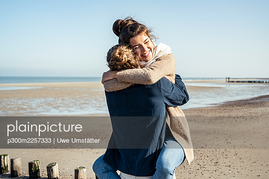 Affectionate young couple embracing each other at beach on sunny day - p300m2257333 by Uwe Umstätter