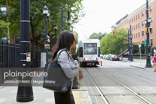 Businesswoman checking time by light rail line - p924m2018660 by Megan Maloy