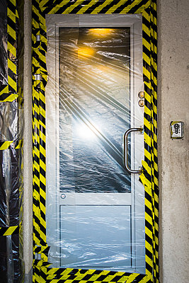 Entrance door covered in plastic and tape - p1418m1492018 by Jan Håkan Dahlström