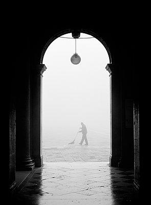 Arbeiter fegt Markusplatz im Nebel, Venedig - p1493m1584572 von Alexander Mertsch