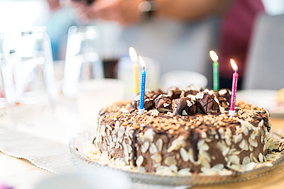 Lighted birthday candles on a cake - p300m2028766 by Christophe Papke