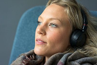 Portrait of young woman listening to music with headphones - p300m2156552 von Robijn Page