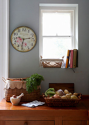 Roger Lascelles clock beside window above vegetables in Georgian townhouse kitchen - p349m789884 by Brent Darby