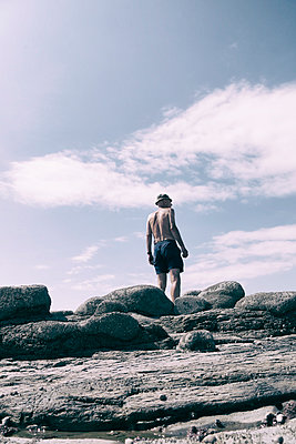 Man in shorts and sun hat standing on rocks - p597m2008080 by Tim Robinson