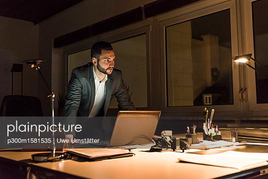 Businessman working in office at night - p300m1581535 von Uwe Umstätter