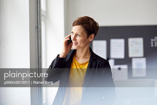 Attractive businesswoman standing in office, using smartphone - p300m2013011 von Rainer Berg