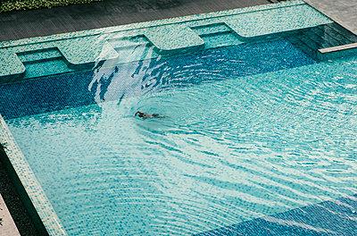 Einzelner Mann schwimmt im Pool - p1130m2007846 von Jonathan Kitchen