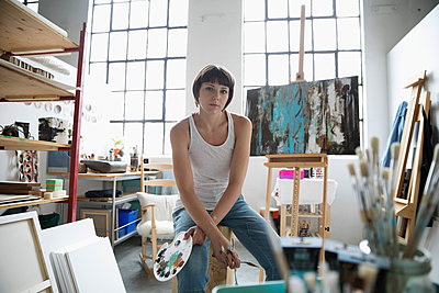 Portrait confident, serious female painter with palette painting at canvas on easel in art studio - p1192m1490240 by Hero Images