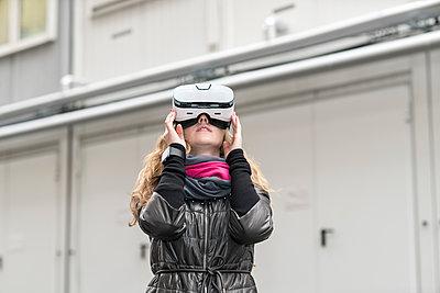 Frau benutzt VR-Brille im Freien - p1332m1445831 von Tamboly