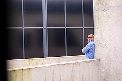 Pensive businessman leaning against concrete wall - p300m1567957 von Jo Kirchherr