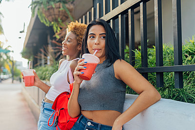 USA, Florida, Miami Beach, two female friends having a soft drink in the city - p300m2069062 von Boy photography