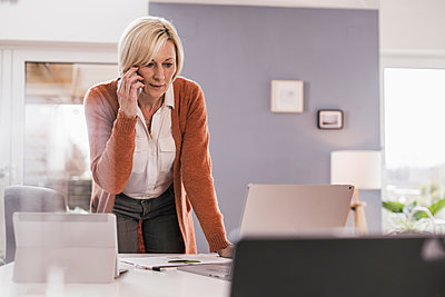 Female professional looking at laptop while discussing over mobile phone in home office - p300m2276640 by Uwe Umstätter