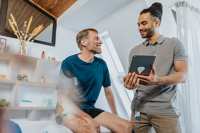 Male physiotherapist with digital tablet smiling at patient in practice - p300m2276809 by Mareen Fischinger