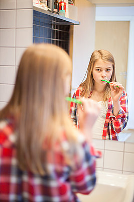 Girl brushing teeth and looking at mirror - p312m1470290 by Christina Strehlow