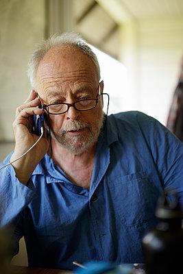Sweden, Senior man talking on phone - p352m1349322 by Gustaf Emanuelsson