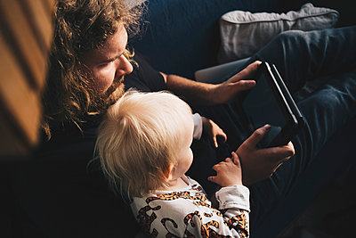 Father showing digital tablet to girl while sitting on sofa at home - p426m1506279 by Maskot