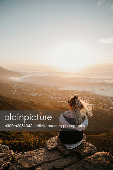 South Africa, Cape Town, Kloof Nek, woman sitting on rock at sunset - p300m2081042 by letizia haessig photography