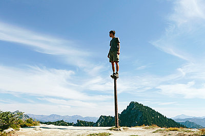 A man standing and balancing on a metal post, looking towards expansive sky, on Surprise Mountain, Alpine Lakes Wilderness, Mt. Baker-Snoqualmie national forest. - p1100m875960f by Paul Edmondson