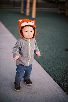 Little boy at the playground wearing a bright orange fox-design hat. - p1166m2162861 by Cavan Images