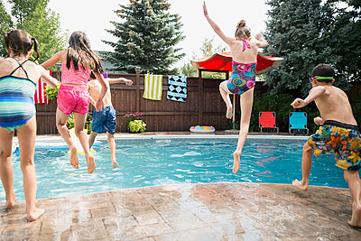 Boys and girls jumping into swimming pool - p1192m1183981 by Hero Images