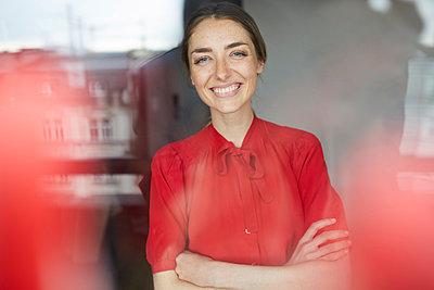 Portrait of laughing woman behind windowpane wearing red blouse - p300m1581616 von Philipp Nemenz
