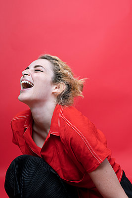 Laughing young woman lin front of red background - p300m2079816 by Jorge Garcia-Romeu Senante