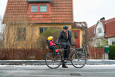 Sweden, Sodermanland, Stockholm, Man holding bicycle with son (2-3) on back seat - p352m1186932 by Julia Sjöberg
