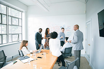 Businessman talking near whiteboard in meeting - p555m1504100 by John Fedele