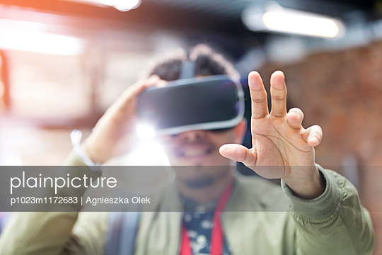 f20511e944e Portrait man trying virtual reality simulator glasses reaching ...