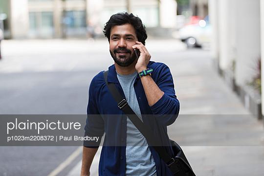 Man with smart phone walking on sidewalk - p1023m2208372 by Paul Bradbury