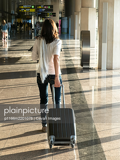 Woman walking with suitcase at the departure hall of the airport. - p1166m2201078 by Cavan Images