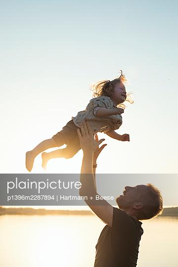 Vater spielt Kind am Wasser - p1396m2287894 von Hartmann + Beese