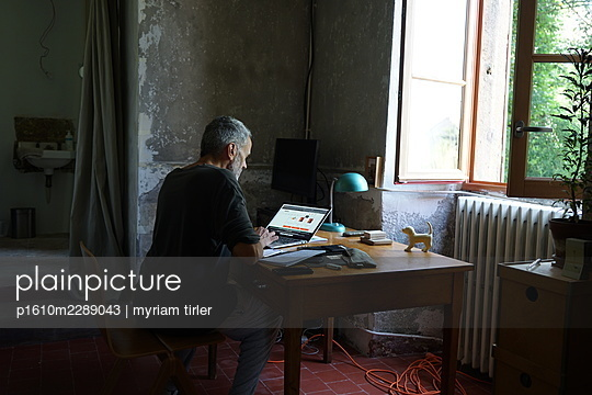 A man works on his computer in the countryside - p1610m2289043 by myriam tirler