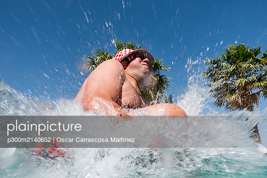 Overweight man jumping into swimming pool - p300m2140652 by Oscar Carrascosa Martinez