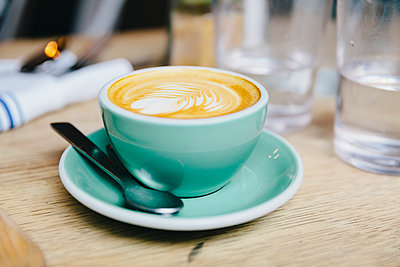 Close-up of frothy drink served in coffee cup on wooden table at cafe - p1166m1567532 by Cavan Images