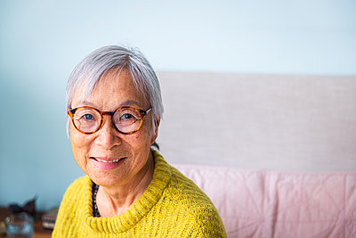 Smiling senior woman wearing yellow sweater sitting in bedroom at home - p1166m2285611 by Cavan Images