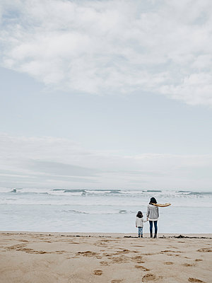 mother and daughter on the beach looking at the sea - p1522m2145000 by Almag