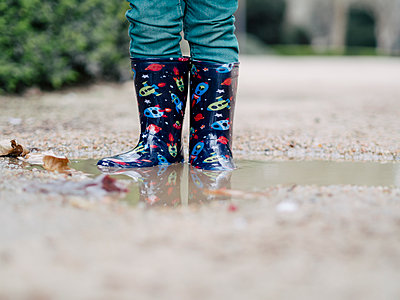 Little boy wearing Wellington boots standing in a puddle, partial view - p300m1140788 by Xose Casal