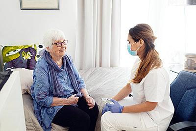 Nurse with elderly woman at home - p312m2299628 by Plattform