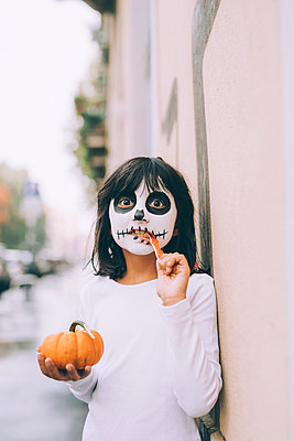 Girl with face paint, eating Halloween candy - p429m2217737 by Eugenio Marongiu