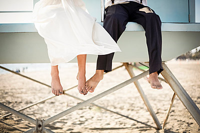 Asian bride and groom sitting on lifeguard hut on beach - p555m1409196 by Shestock