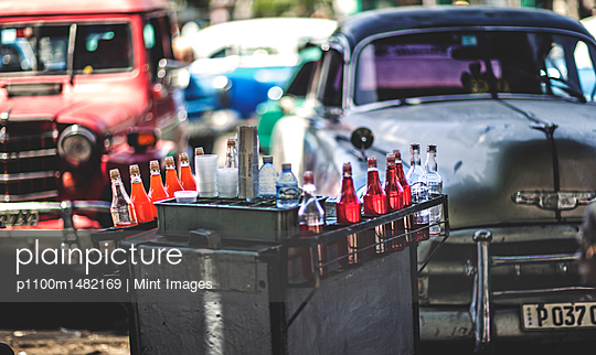 A drinks cart in front of parked classic 1950s cars.