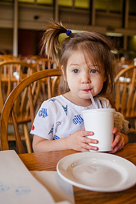 a cute little girl sips a drink out of a straw at a restaurant table - p1166m2084889 by Cavan Images