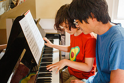 A boy and father sit close together at piano playing music at home - p1166m2261274 by Cavan Images