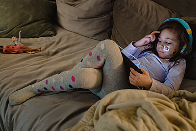 Young girl looking at iPad with headphones - p1166m2261683 by Cavan Images